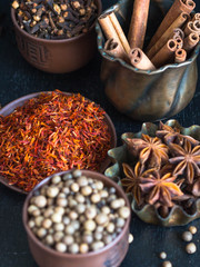 Various spices - cinnamon, star anise, cloves, saffron, allspice in a bowl on a dark background