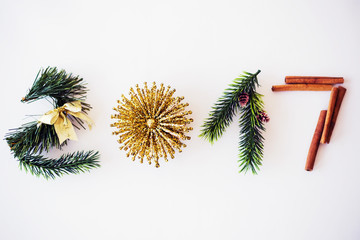 2017 text made with green pine, cinnamon and golden christmas toy