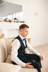 Groom sitting on the sofa waiting for the bride on his wedding day. at wedding tuxedo smiling and waiting for bride.Elegant man in black costume and bow-tie. Groom in a suit holding buttonhole.