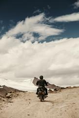Lonely motocyclist traveler on mountain rosad in Himalaya