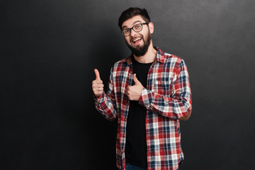 Man standing over chalkboard and make thumbs up gesture.