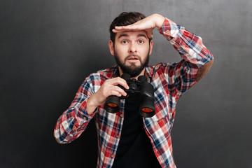 Man in plaid shirt holding binoculars and looking far away Wall mural