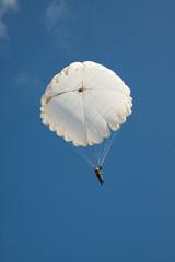 White round parachute on background blue sky.