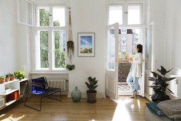 Woman at home standing at balcony door