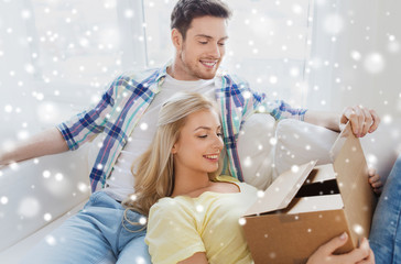 happy couple with cardboard box or parcel at home