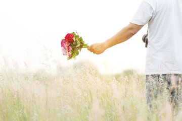 Man wearing a white T-Shirt, hanging camera strap, walking in the middle of meadow, holding Roses bouquet and touching on the top of the flowers during a sunset