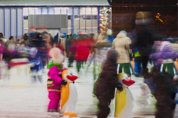 Funny kids, families together in evening time outdoors in the park on winter skating rink, motion blur