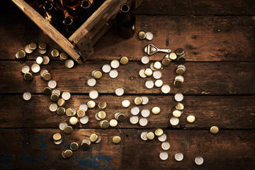 Scattered bottle tops and a crate of empty bottles
