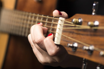 Young woman clamped with fingers guitar strings