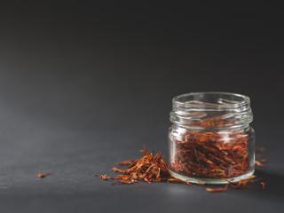 Small jar of saffron on a dark background