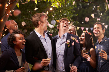Smiling people celebrating wedding party in backyard
