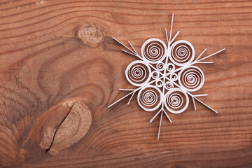 Paper snowflake made with quilling technique on a wooden surface
