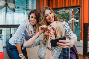 Three Happy cute girl friends Taking Selfie In Cafe. The concept of modern friendship and relations between women