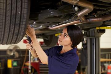 Female Auto Mechanic Working Underneath Car In Garage