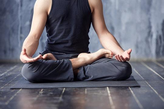 Young men do yoga indoors on black mat
