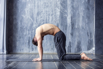 Yoga men workout on black mat.