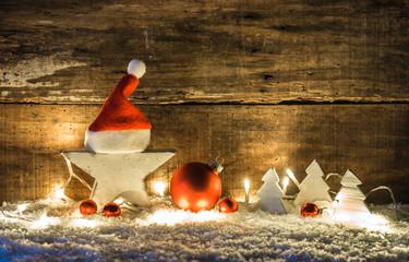 Weihnachten Lichter Holz Stern mit Santa Mütze und Weihnachtsschmuck im Schnee