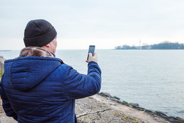 man photographing seascape by mobile phone