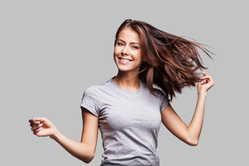 Pretty girl with long hair laughing, dancing and having fun