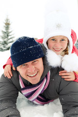 Happy family riding on snow slides in winter time