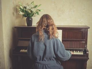 Woman in bathrobe playing piano