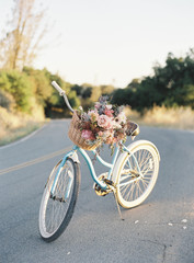 Bicycle on stand, fresh flowers in basket at front of bicycle