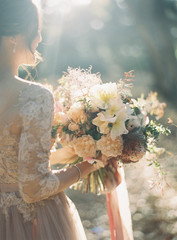 Bride standing in rural setting, holding bouquet, rear view