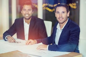 Portrait of businessmen sitting at their desk