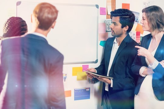 Group of businesspeople looking at whiteboard