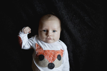 Portrait of baby flexing muscles