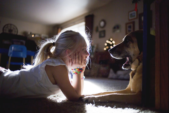 Girl lying on floor, face to face with pet dog
