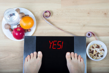 """Digital scales with female feet on them and sign""""yes!"""" surrounded by glass of water, plates with nuts, fruits, muesli and measuring tape."""