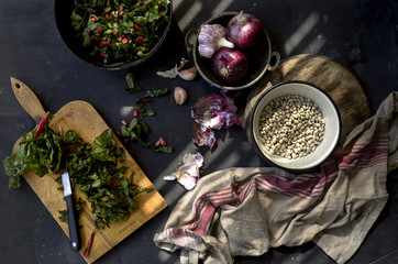Bowl of black eyed peas, red onions, garlic and chard, overhead view