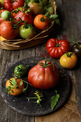 Tomatoes in basket, on wooden table, still life