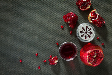 Pomegranate and pomegranate juice on a concrete gray background.