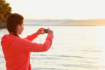 Young woman makes photo at beach after run