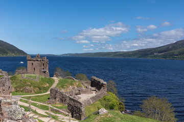 Loch Ness, Scotland - June 2, 2012: Shot of the wider deep blue Loch Ness with part of Urquhart Castle ruins in the foreground. Green surrounding hills. Light blue sky.