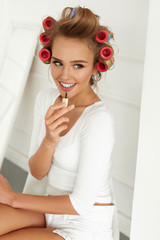 Beauty. Girl With Hair Curlers Curling Hair, Putting Lip Gloss