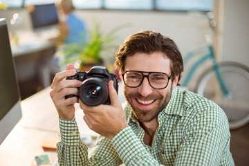 Graphic designer clicking photo from digital camera