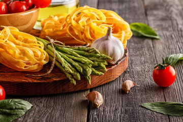 Products for cooking - fresh asparagus, pasta, olive oil.