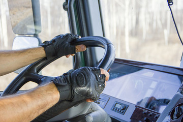 Closeup view from the truck cab. Truck driver keeps driving wheel with both hands