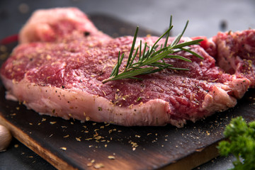Raw beef steak with rosemary and garlic on cutting board on dark background