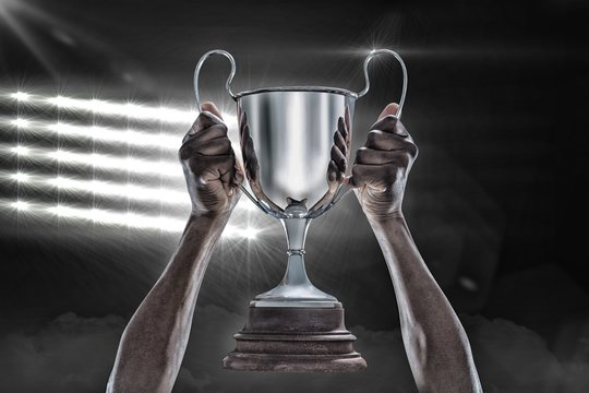 Composite image 3D of cropped hand of athlete holding trophy