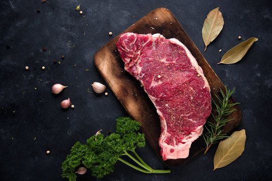 Raw steak with rosemary, salt and pepper cooking over stone table background