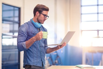 Business executive having coffee and looking at laptop