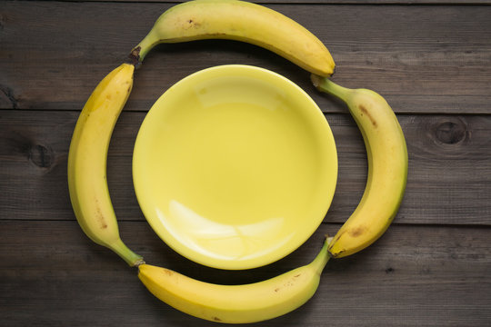 four yellow bananas lay around empty yellow plate on wooden background