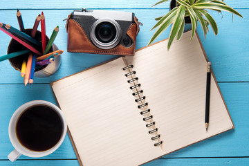 Office desk table with notepad, camera, cup of coffee and flower on wooden table background