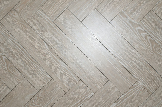 Beige floor tiles arranged in herringbone with look of parquet