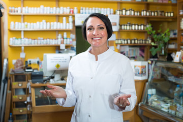 Woman seller in uniform standing in pharmaceutical  store