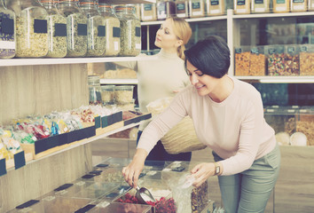 Women picking nuts and dried fruits in store.